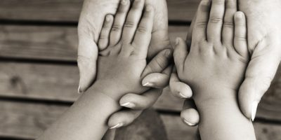 Adult's hands holding child's hands, mature adult, child aged 2 to 3 years
